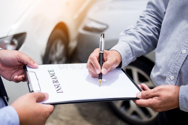 L'agente di assicurazione auto invia ad una penna al suo segno dei clienti il insuran fotografie stock
