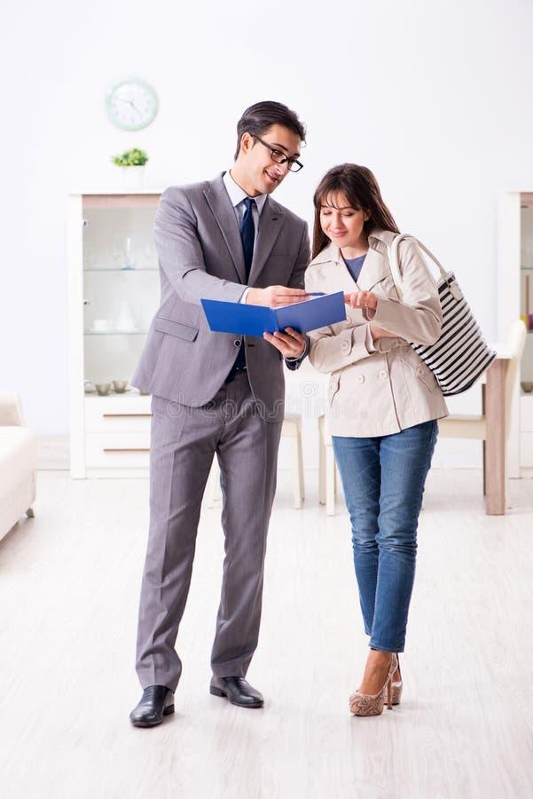 L'agente immobiliare che mostra la nuova proprietà dell'appartamento al cliente immagine stock