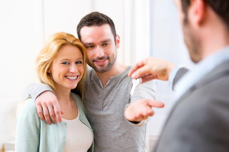 L'agente immobiliare consegna le chiavi di nuova casa alle giovani coppie immagine stock libera da diritti