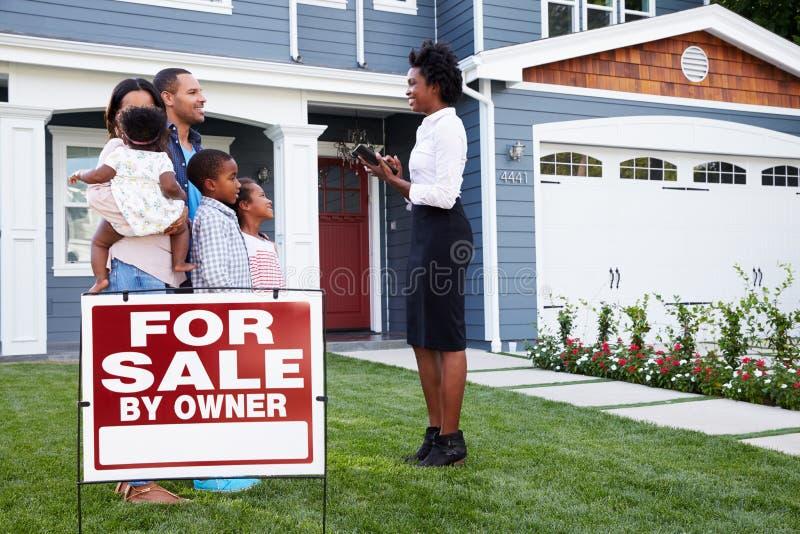 L'agente immobiliare e la famiglia fuori della casa con un ½ del ¿ del ï per il ½ del ¿ del saleï firmano immagini stock libere da diritti