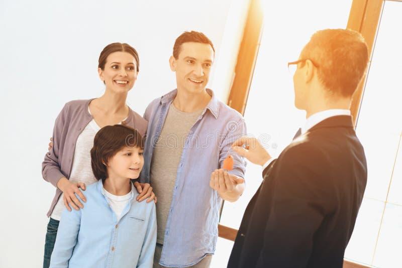 L'agente immobiliare sta fornendo le chiavi alla famiglia in nuovo appartamento con le scatole di cartone immagine stock