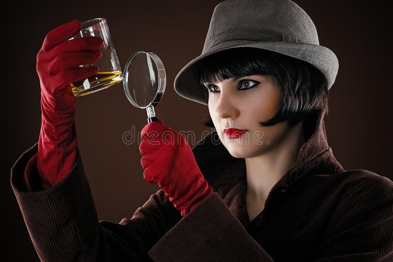 L'agente investigativo della donna esamina fotografie stock