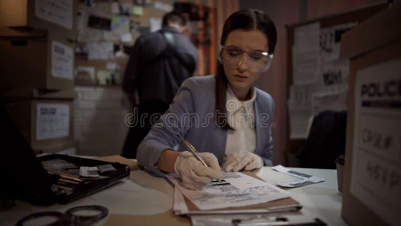L'agente investigativo di signora che controlla il criminale prende le impronte digitali alla base di dati, esaminante la prova immagini stock