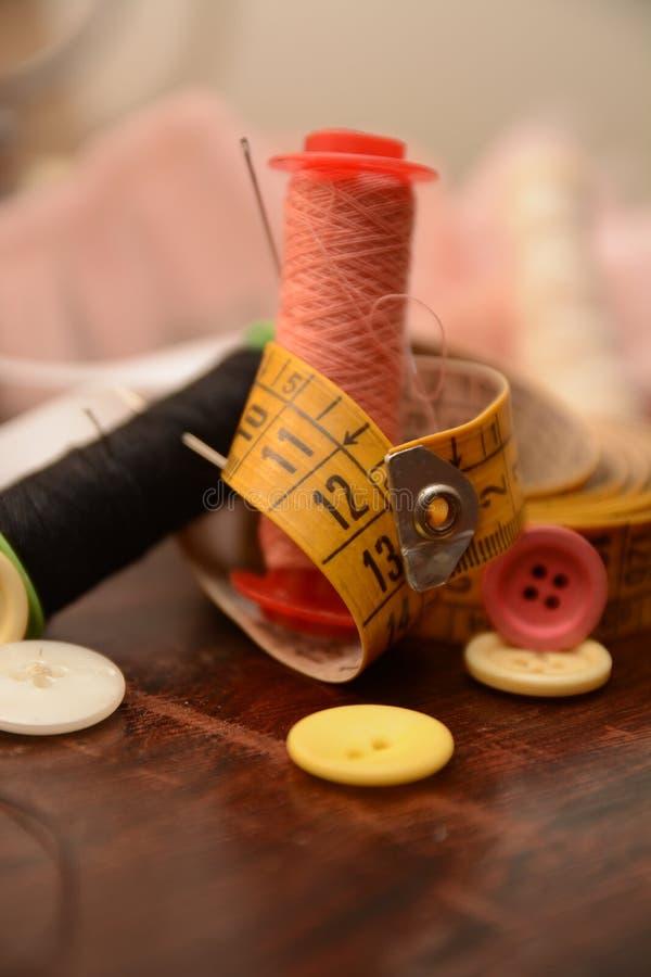 L'ago dei bottoni del cotone per cuce l'adattamento del lavoro del vestito da modo fotografie stock libere da diritti