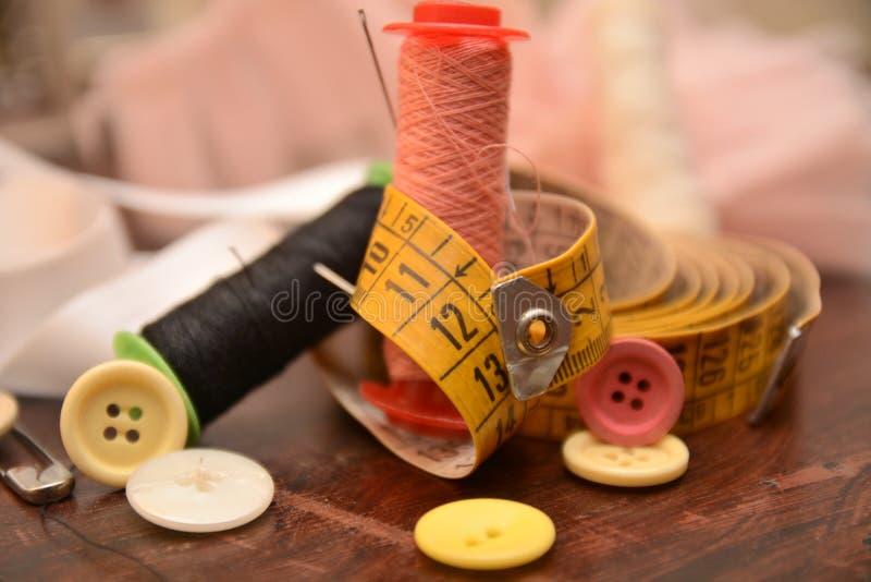 L'ago dei bottoni del cotone per cuce l'adattamento del lavoro del vestito da modo immagini stock libere da diritti