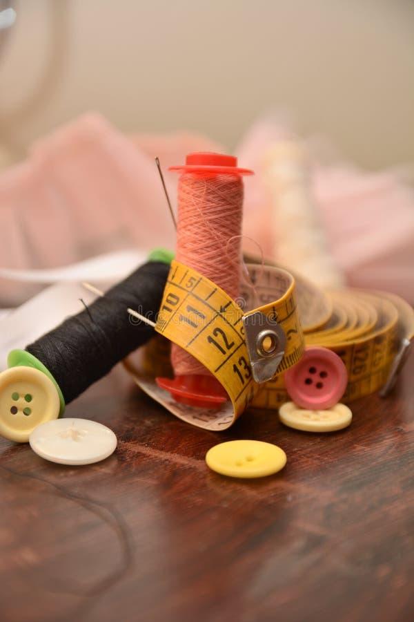 L'ago dei bottoni del cotone per cuce l'adattamento del lavoro del vestito da modo fotografia stock libera da diritti