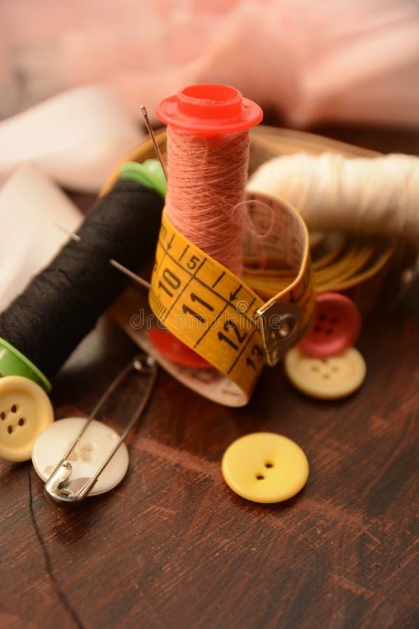 L'ago dei bottoni del cotone per cuce l'adattamento del lavoro del vestito da modo immagini stock