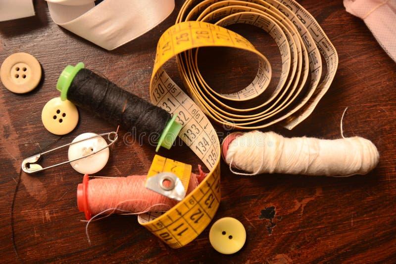 L'ago dei bottoni del cotone per cuce l'adattamento del lavoro del vestito da modo immagine stock