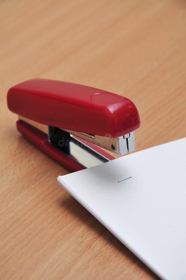 L'agrafeuse rouge attache le livre blanc photos libres de droits