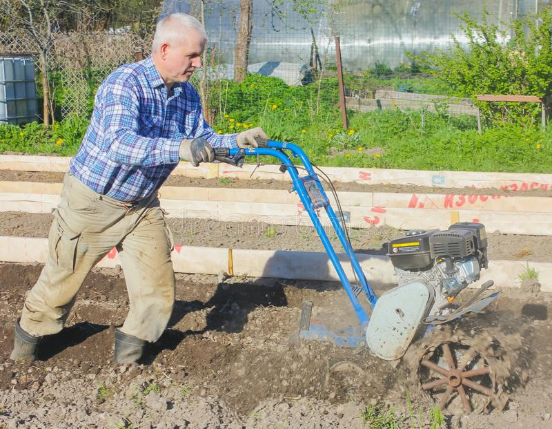 L'agricoltore ara la terra con un motore-blocco Aratura del grou fotografia stock libera da diritti