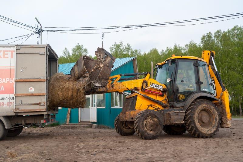 L'agricoltore sui carichi del trattore rivolta il fieno nel furgone fotografie stock