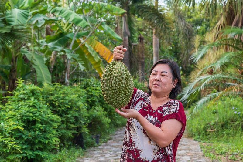 L'agriculteur asiatique tenant le durian est un roi de fruit photo stock