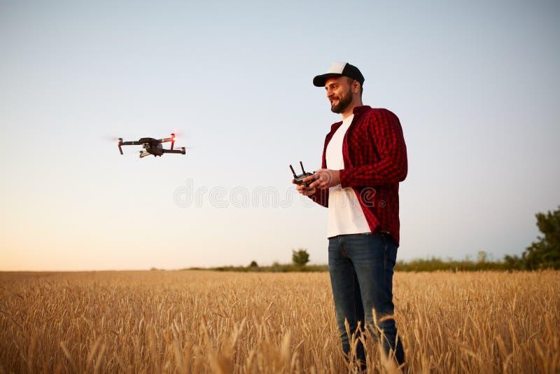 L'agriculteur tient le contrôleur à distance avec ses mains tandis que le quadcopter vole sur le fond Le bourdon plane derrière images stock