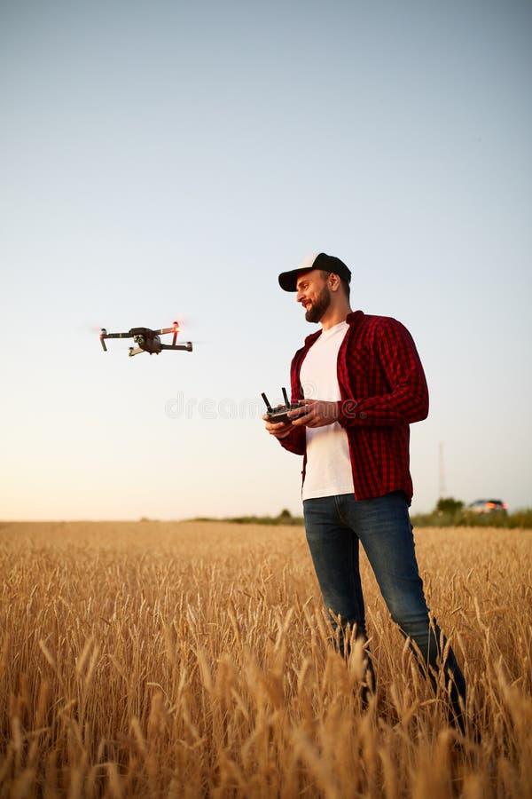 L'agriculteur tient le contrôleur à distance avec ses mains tandis que le quadcopter vole sur le fond Le bourdon plane derrière photographie stock