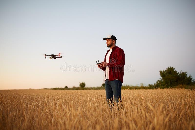 L'agriculteur tient le contrôleur à distance avec ses mains tandis que le quadcopter vole sur le fond Le bourdon plane derrière photographie stock libre de droits