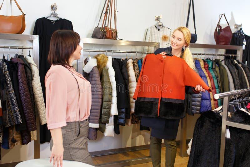 L'aide d'employé de magasin choisit des vêtements images stock