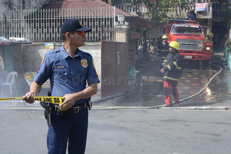 L'aide de policier maintiennent l'ordre pendant le feu de maison qui a étripé les maisons intérieures d'hutte photo libre de droits