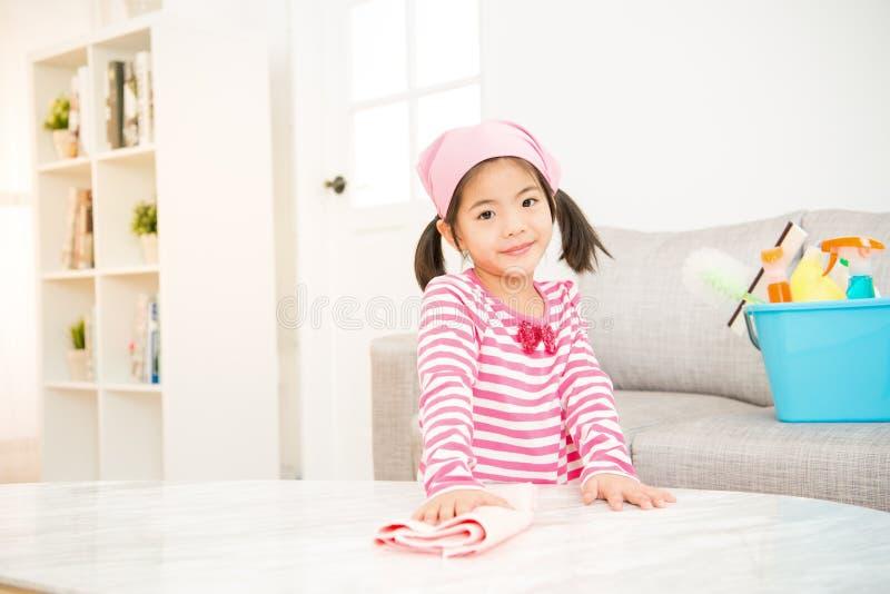 L'aide mignonne de petite fille font le nettoyage image stock
