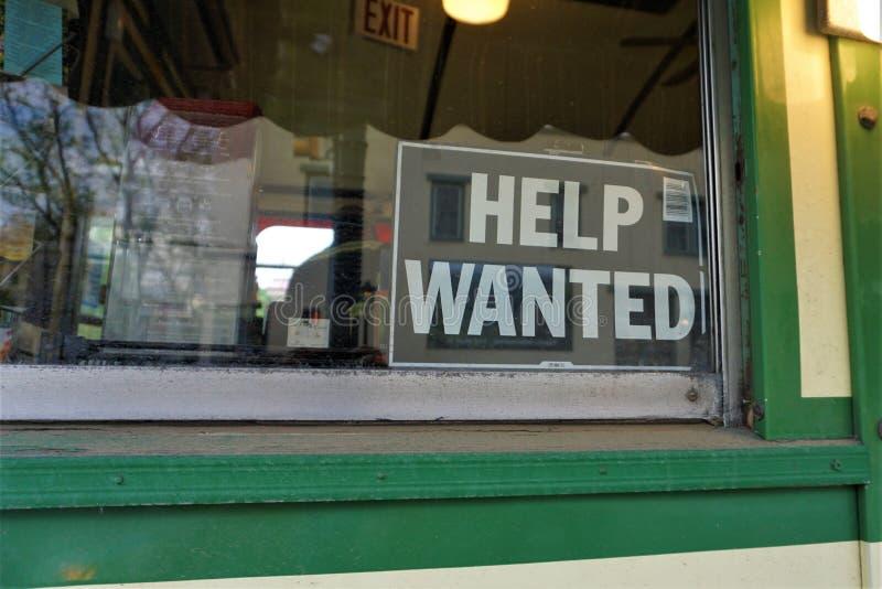 L'aide voulue signent dans la fenêtre de la petite entreprise photographie stock libre de droits