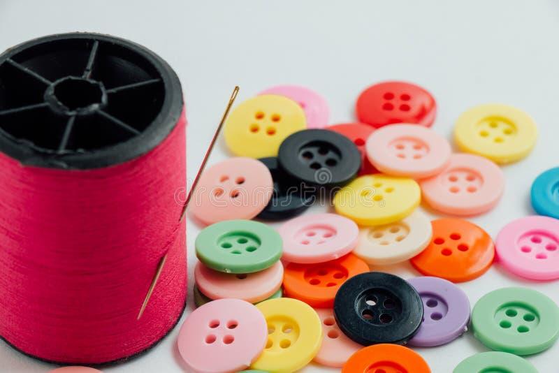 L'aiguille avec la bobine de fil du fil et des boutons, cousent l'instrument photo libre de droits
