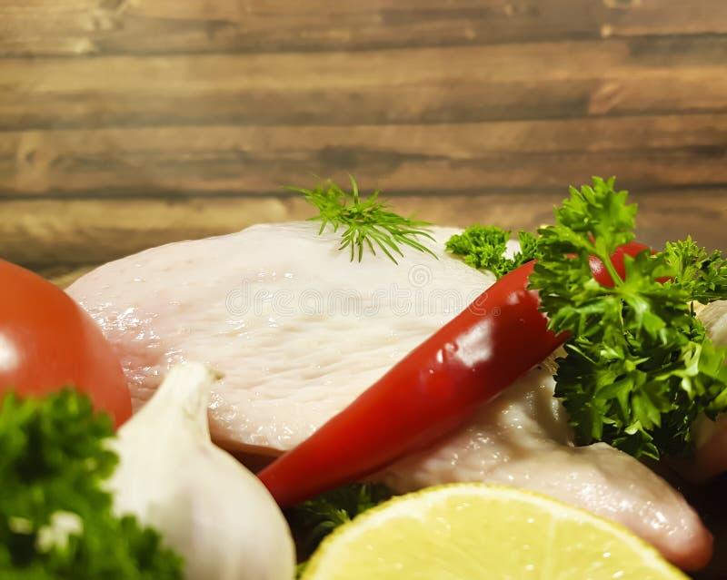 L'ail cru de jambe de poulet de viande verdit le plat de romarin de citron, poivre de piment rouge, tomate de nutrition photo stock