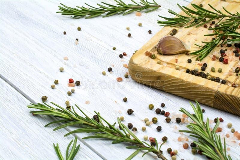 L'ail, planche à découper un mélange des poivrons sur un fond en bois blanc image libre de droits