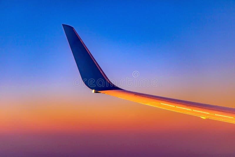 L'aile avec la dérive de l'avion au coucher du soleil image libre de droits