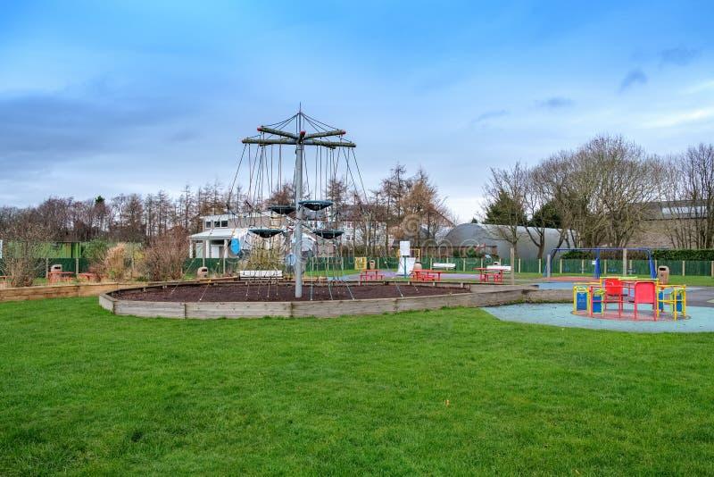 L'aire de jeux des enfants modernes avec la vue de s'élever entourée par des arbres en hiver photos libres de droits