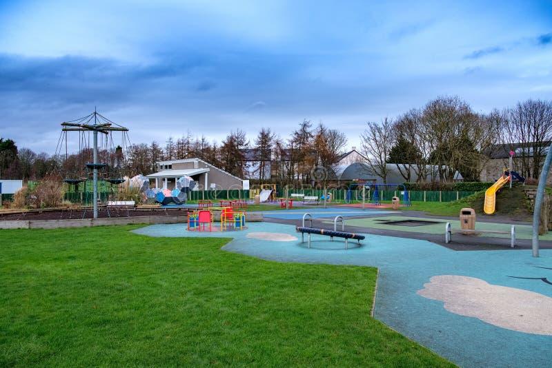 L'aire de jeux des enfants modernes entourée par des arbres en hiver image stock