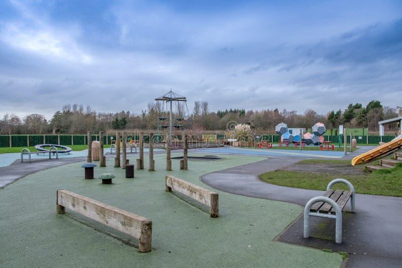 L'aire de jeux des enfants modernes entourée par des arbres en hiver photographie stock
