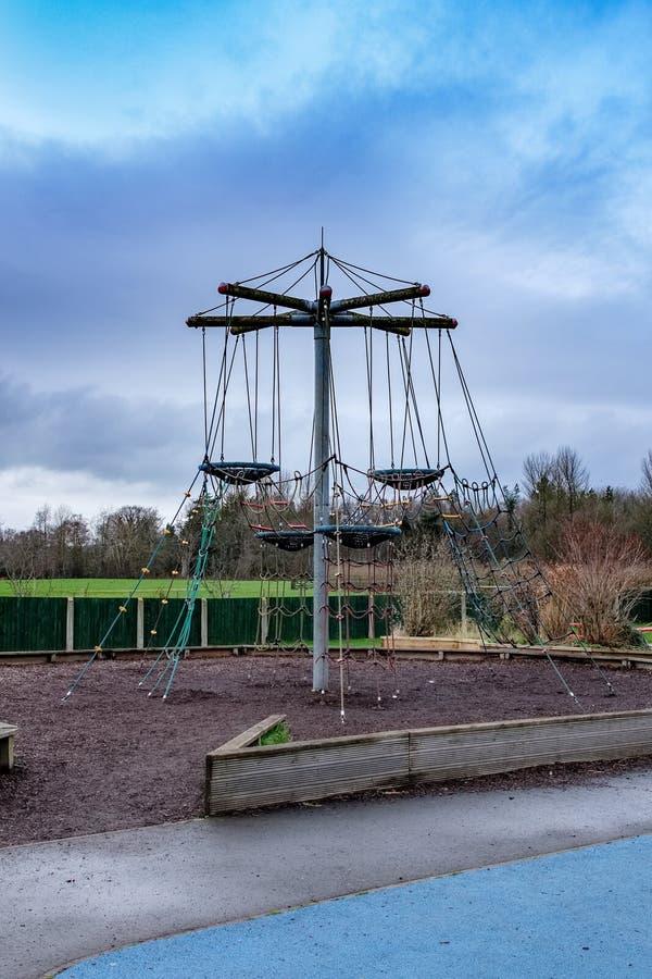 L'aire de jeux des enfants modernes entourée par des arbres en hiver images stock