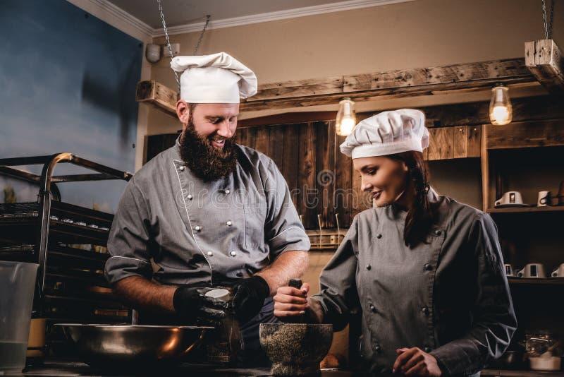 L'aiuto cuoco frantuma i semi di sesamo in un mortaio per la cottura del pane Cuoco unico che insegna al suo assistente a cuocere immagine stock