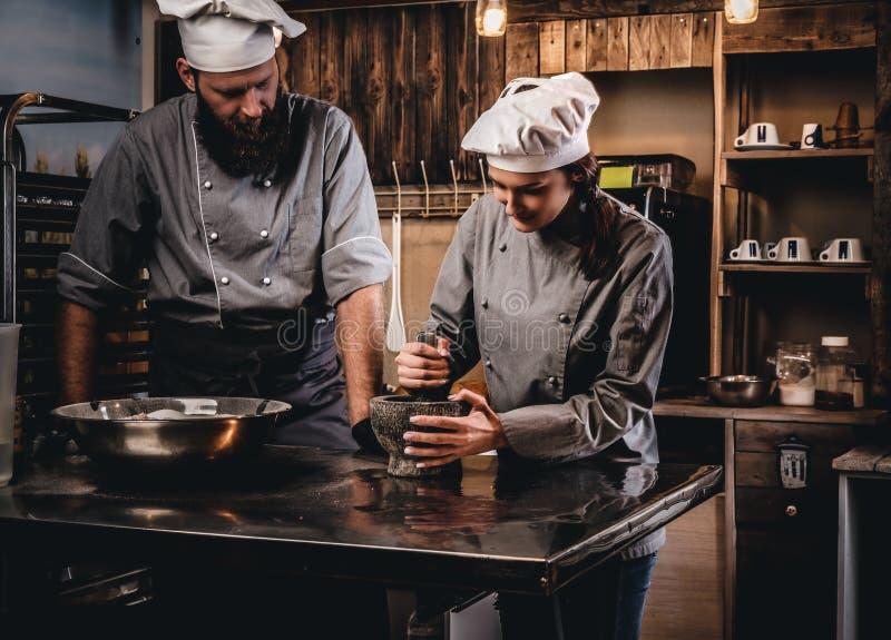 L'aiuto cuoco frantuma i semi di sesamo in un mortaio per la cottura del pane Cuoco unico che insegna al suo assistente a cuocere fotografia stock
