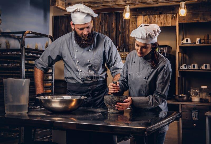 L'aiuto cuoco frantuma i semi di sesamo in un mortaio per la cottura del pane Cuoco unico che insegna al suo assistente a cuocere immagini stock libere da diritti