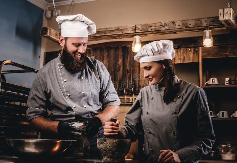 L'aiuto cuoco frantuma i semi di sesamo in un mortaio per la cottura del pane Cuoco unico che insegna al suo assistente a cuocere immagini stock