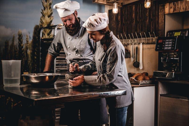 L'aiuto cuoco frantuma i semi di sesamo in un mortaio per la cottura del pane Cuoco unico che insegna al suo assistente a cuocere fotografie stock libere da diritti