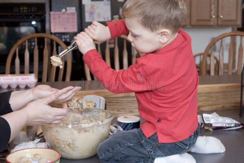 L'aiuto del ragazzo produce i biscotti immagine stock
