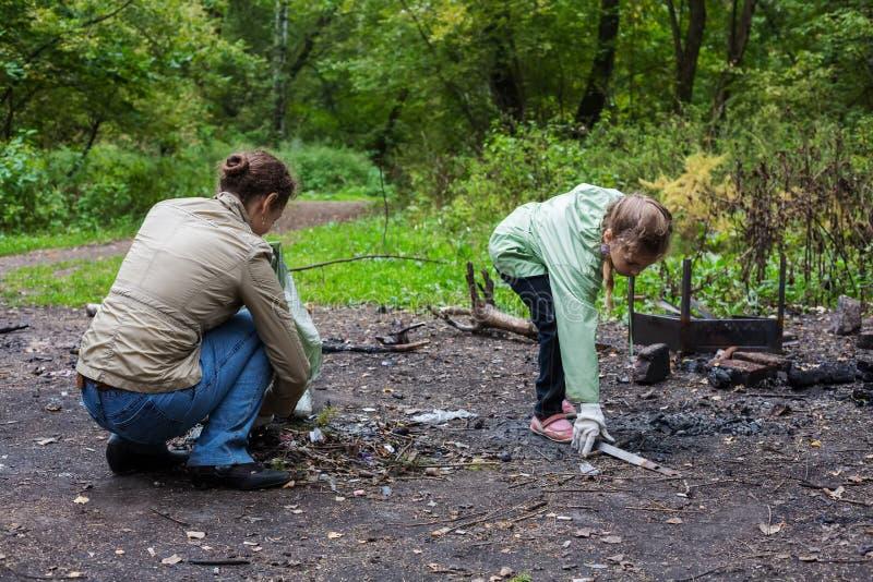 L'aiuto della figlia e della madre pulisce la foresta fotografie stock
