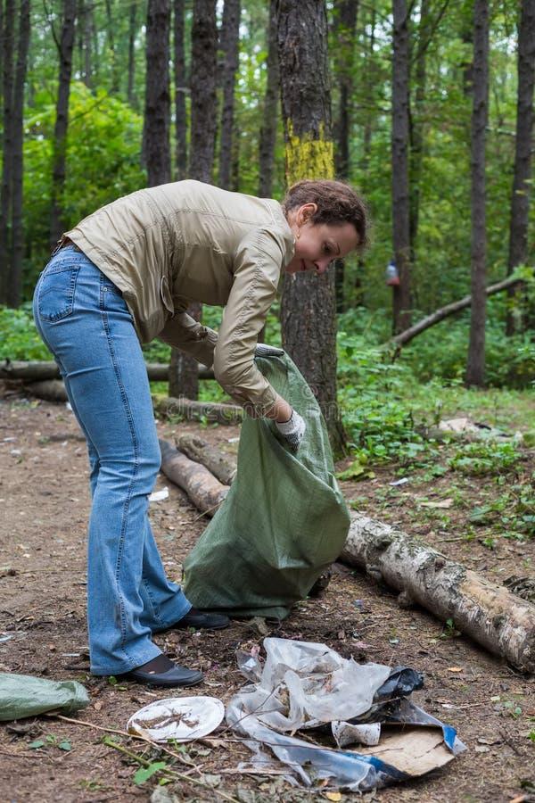 L'aiuto della ragazza pulisce la foresta fotografia stock libera da diritti