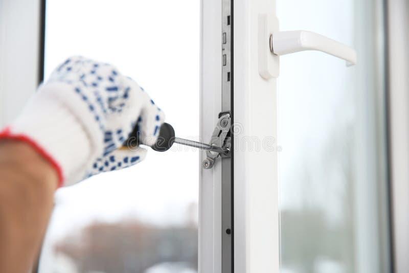 L'ajustement de travailleur de la construction a installé la fenêtre avec le tournevis à l'intérieur photographie stock libre de droits