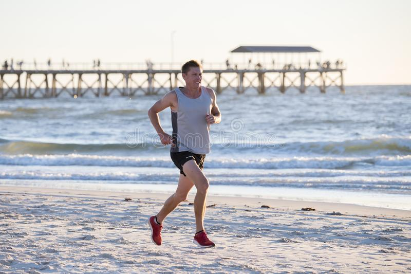 L'ajustement sportif et le coureur fort équipent la formation sur la plage de coucher du soleil d'été dans le fonctionnement de b photographie stock libre de droits