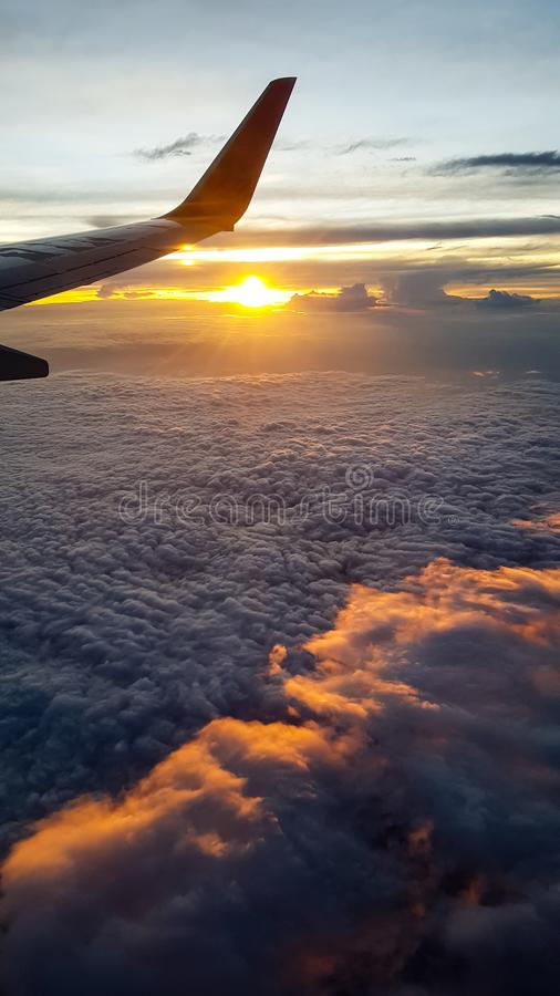 L'ala dell'æreo a reazione sorvola il cielo del tramonto sopra la nuvola fotografia stock libera da diritti