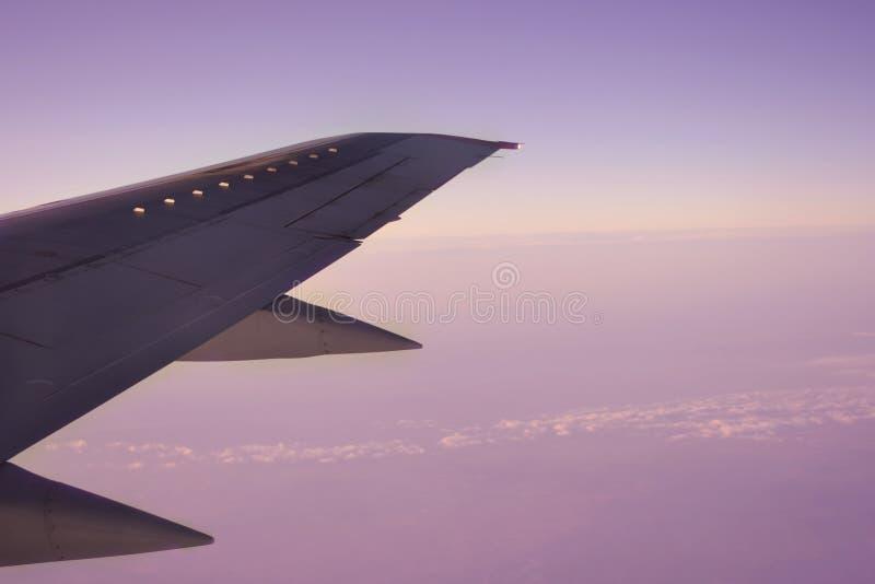 L'ala di un volo dell'aeroplano sopra la mattina si appanna immagine stock libera da diritti