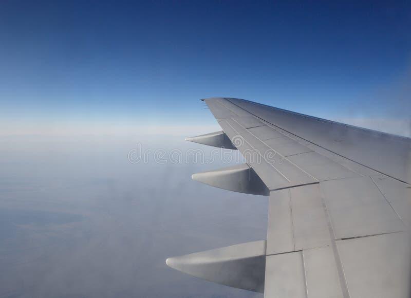 L'ala di un volo dell'aeroplano sopra la mattina si appanna immagine stock