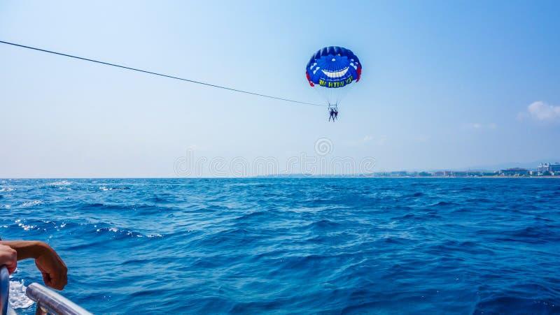 L'ala variopinta del parasail ha tirato in barca nel mare Alany acqua fotografia stock