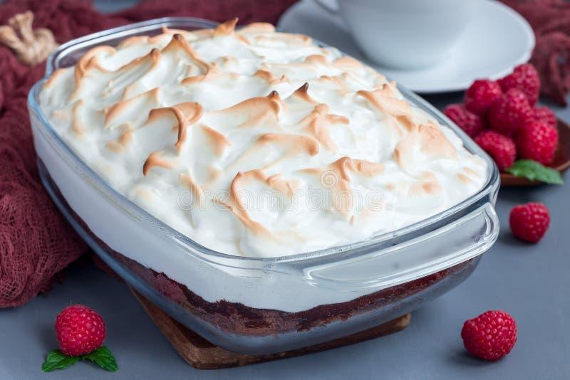 L'Alaska cuit au four avec le gâteau mousseline de chocolat, la crème glacée de framboise et photos stock