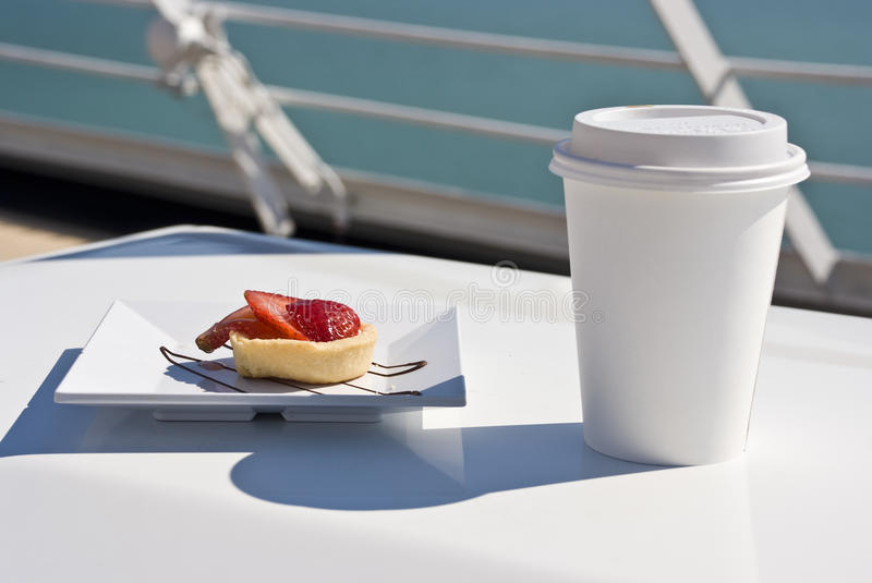 L'Alaska - plaisir avec une fraise Mini Tart And Hot Drink sur la plate-forme photo stock