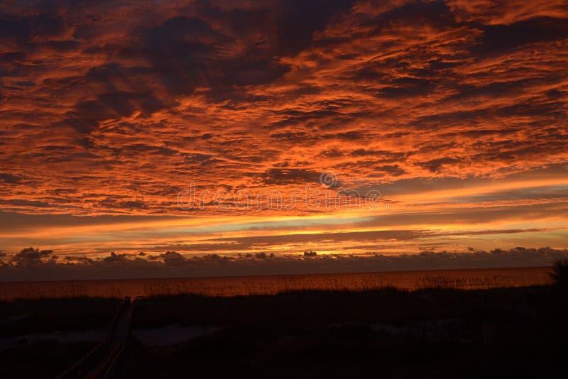 L'alba porta un'esposizione incredibile dei colori vivi sopra le acque dell'isola qui sotto immagini stock