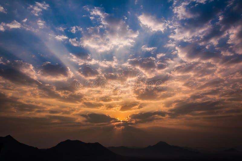 L'alba rays sulla nuvola arancio blu del cielo di mattina con la montagna fotografia stock