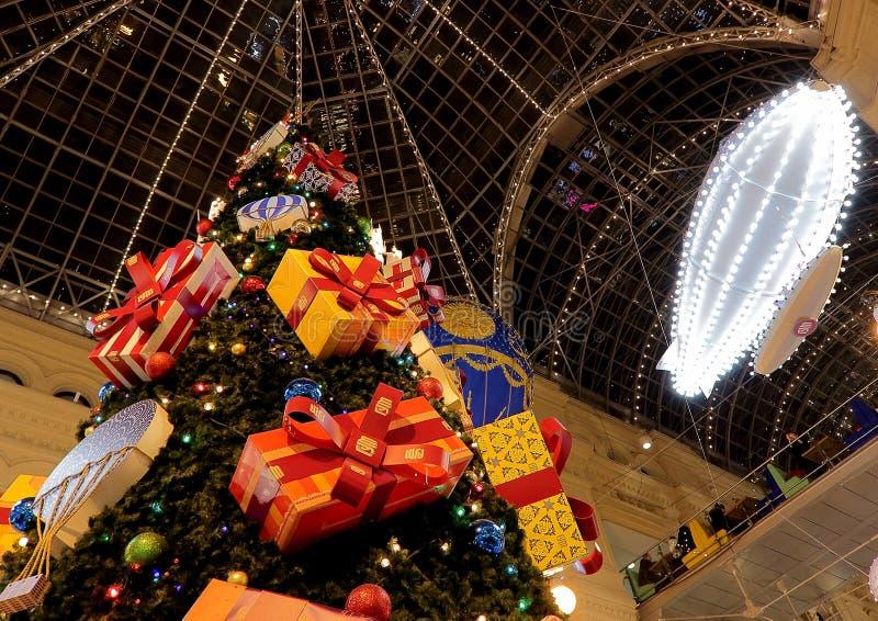 L'albero del nuovo anno e di Natale e la decorazione del deposito universale principale GOMMANO sul quadrato rosso fotografia stock